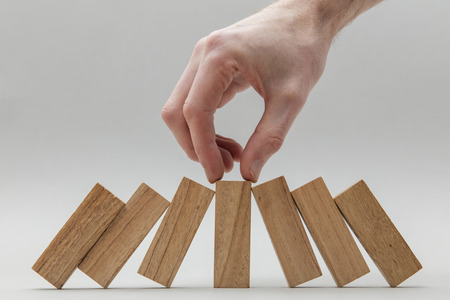 Male hand stopping wooden blocks falling over Stock Photo