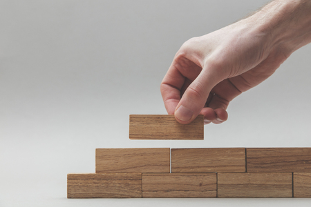 Male hand stacking wooden blocks. Business development and growth concept Imagens