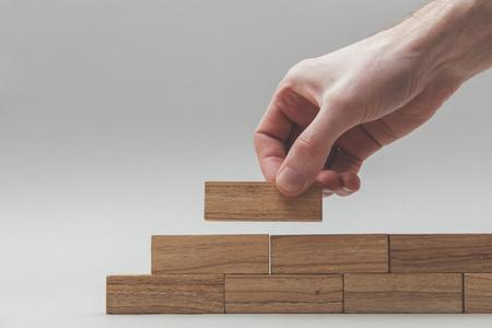 Mannelijke hand die houten blokken stapelt. Bedrijfsontwikkeling en groeiconcept Stockfoto