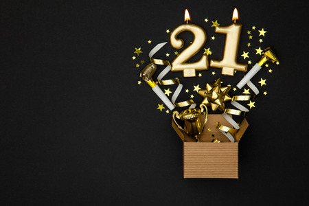 Number 21 gold celebration candle and gift box background Stock Photo