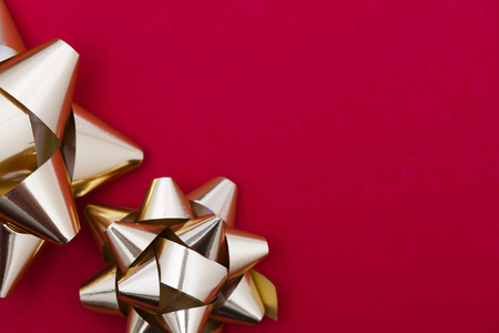 Metallic gift bow on a red background Stock Photo