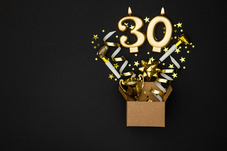 Number 30 gold celebration candle and gift box background