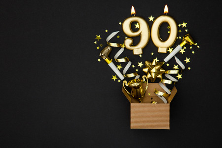 Number 90 gold celebration candle and gift box background