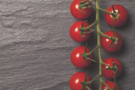 Red cherry vine tomatos on a slate background Stock Photo