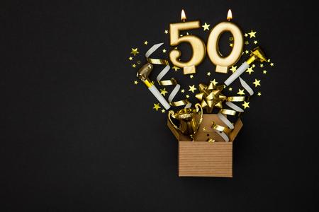Nummer 50 gouden vieringskaars en achtergrond van de giftdoos Stockfoto
