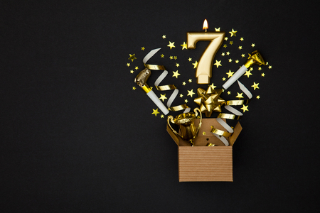 Number 7 gold celebration candle and gift box background Stock Photo - 91935384