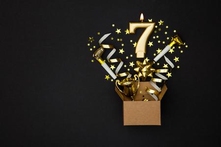 Nummer 7 gouden vieringskaars en giftdoosachtergrond Stockfoto