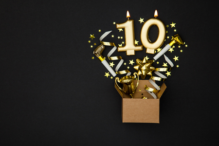 Number 10 gold celebration candle and gift box background