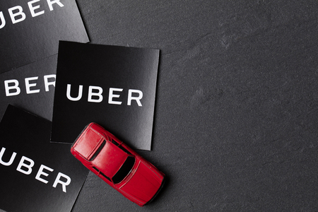 A photograph of  the Uber logo and toy car. Uber is a popular taxi style transport service application, founded in 2009