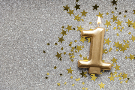 Number 1 gold celebration candle on star and glitter background Stock Photo