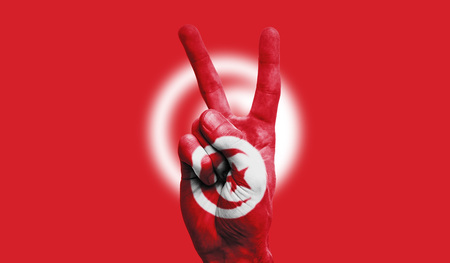 Tunisia national flag painted onto a male hand showing a victory, peace, strength sign
