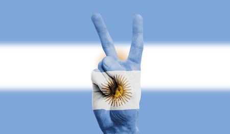 argentina national flag painted onto a male hand showing a victory, peace, strength sign
