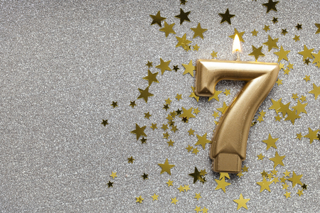 Number 7 gold celebration candle on star and glitter background