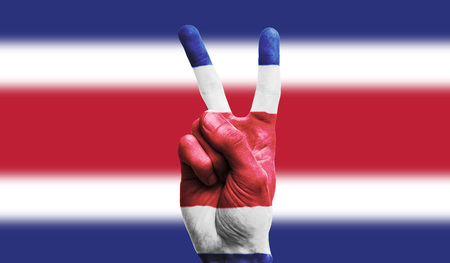 Costa Rica national flag painted onto a male hand showing a victory, peace, strength sign
