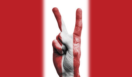 Peru national flag painted onto a male hand showing a victory, peace, strength sign