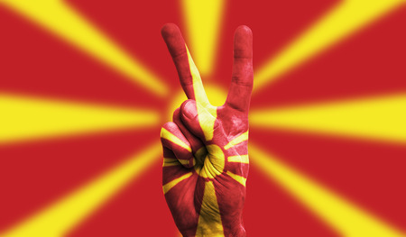 Macedonia national flag painted onto a male hand showing a victory, peace, strength sign