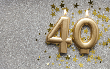Number 40 gold celebration candle on star and glitter background