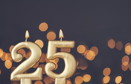Gold number 25 celebration candle against blurred light background