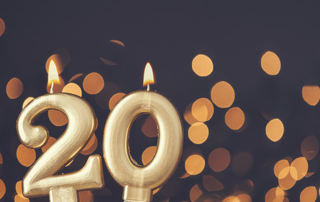 Gold number 20 celebration candle against blurred light background Imagens - 92333203