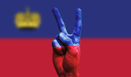 Liechtenstein national flag painted onto a male hand showing a victory, peace, strength sign