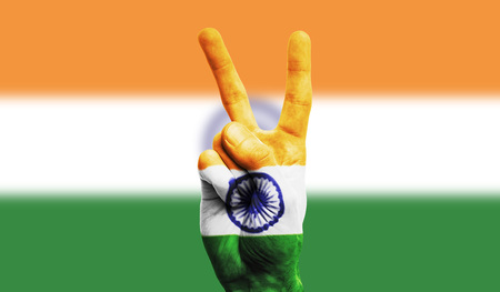 India national flag painted onto a male hand showing a victory, peace, strength sign