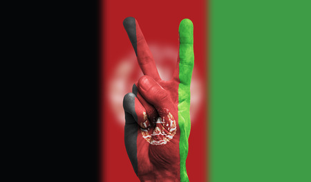 afghanistan national flag painted onto a male hand showing a victory, peace, strength sign
