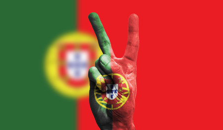 Portugal national flag painted onto a male hand showing a victory, peace, strength sign