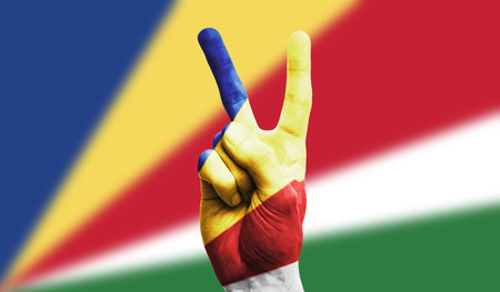 Seychelles national flag painted onto a male hand showing a victory, peace, strength sign