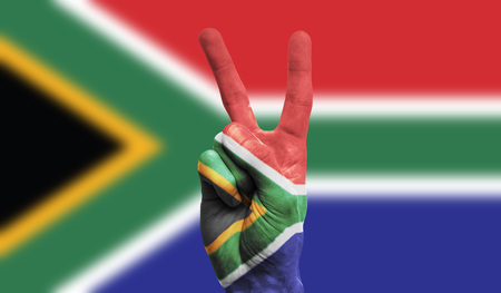 South Africa national flag painted onto a male hand showing a victory, peace, strength sign Stockfoto