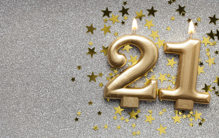 Number 21 gold celebration candle on star and glitter background