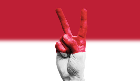 Indonesia national flag painted onto a male hand showing a victory, peace, strength sign