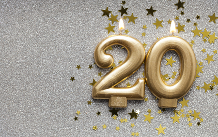 Number 20 gold celebration candle on star and glitter background