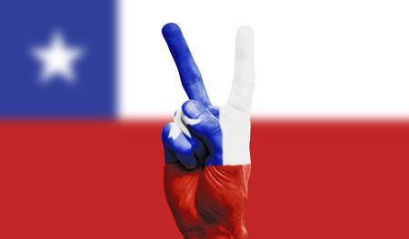 Chile national flag painted onto a male hand showing a victory, peace, strength sign