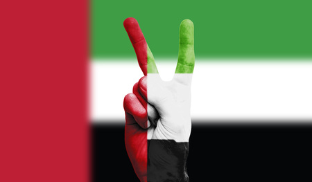UAE national flag painted onto a male hand showing a victory, peace, strength sign