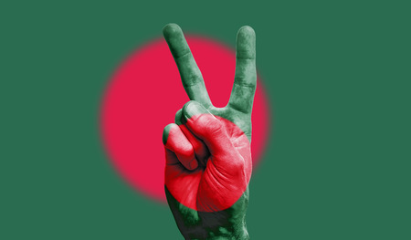 bangladesh national flag painted onto a male hand showing a victory, peace, strength sign