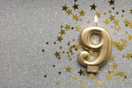 Number 9 gold celebration candle on star and glitter background Stock fotó