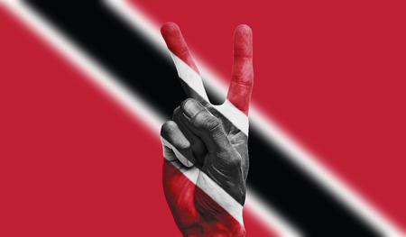 Trinidad national flag painted onto a male hand showing a victory, peace, strength sign Stock Photo