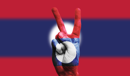 Laos national flag painted onto a male hand showing a victory, peace, strength sign