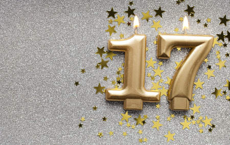 Number 17 gold celebration candle on star and glitter background