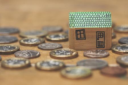 Huismodel met munten. Home financiën concept Stockfoto - 92501199