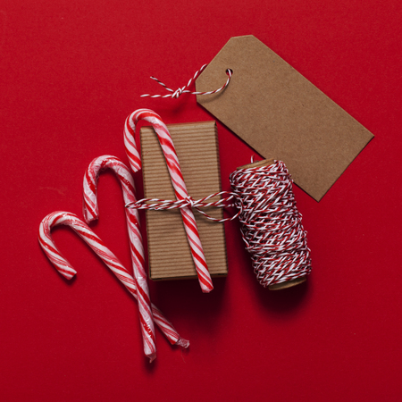 Festive Christmas present with candy cane on a red background