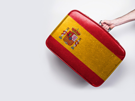 Spain flag on a vintage leather suitcase.