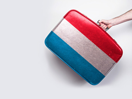 Luxembourg flag on a vintage leather suitcase.