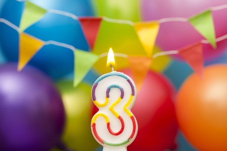 Happy Birthday number 3 celebration candle with colorful balloons and bunting Standard-Bild