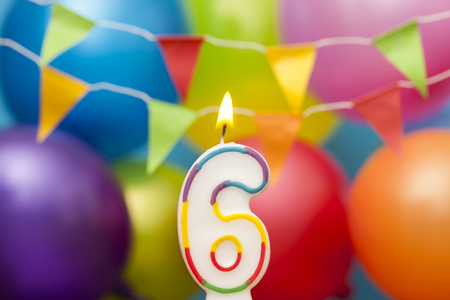 Happy Birthday number 6 celebration candle with colorful balloons and bunting