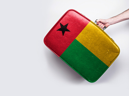 Guinea Bissau flag on a vintage leather suitcase. Stock Photo