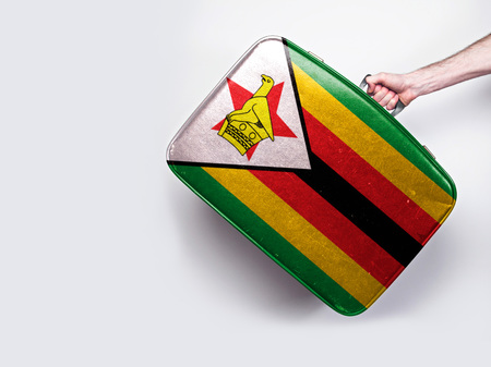 Zimbabwe flag on a vintage leather suitcase. Stock Photo