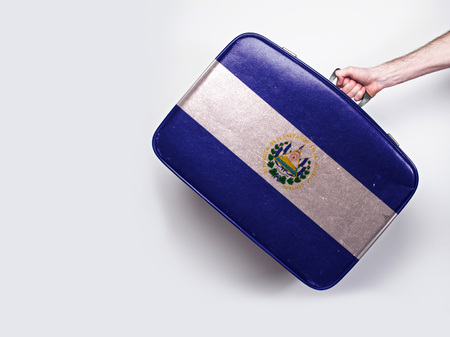 El Salvador flag on a vintage leather suitcase. Stock Photo