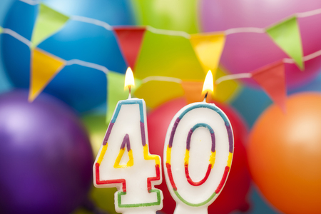 Happy Birthday number 40 celebration candle with colorful balloons and bunting