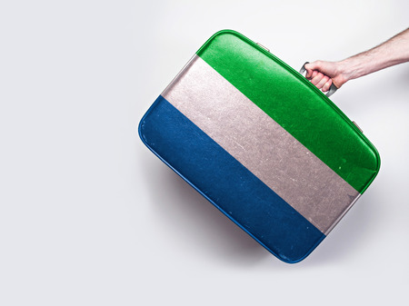Sierra Leone flag on a vintage leather suitcase. Stock Photo